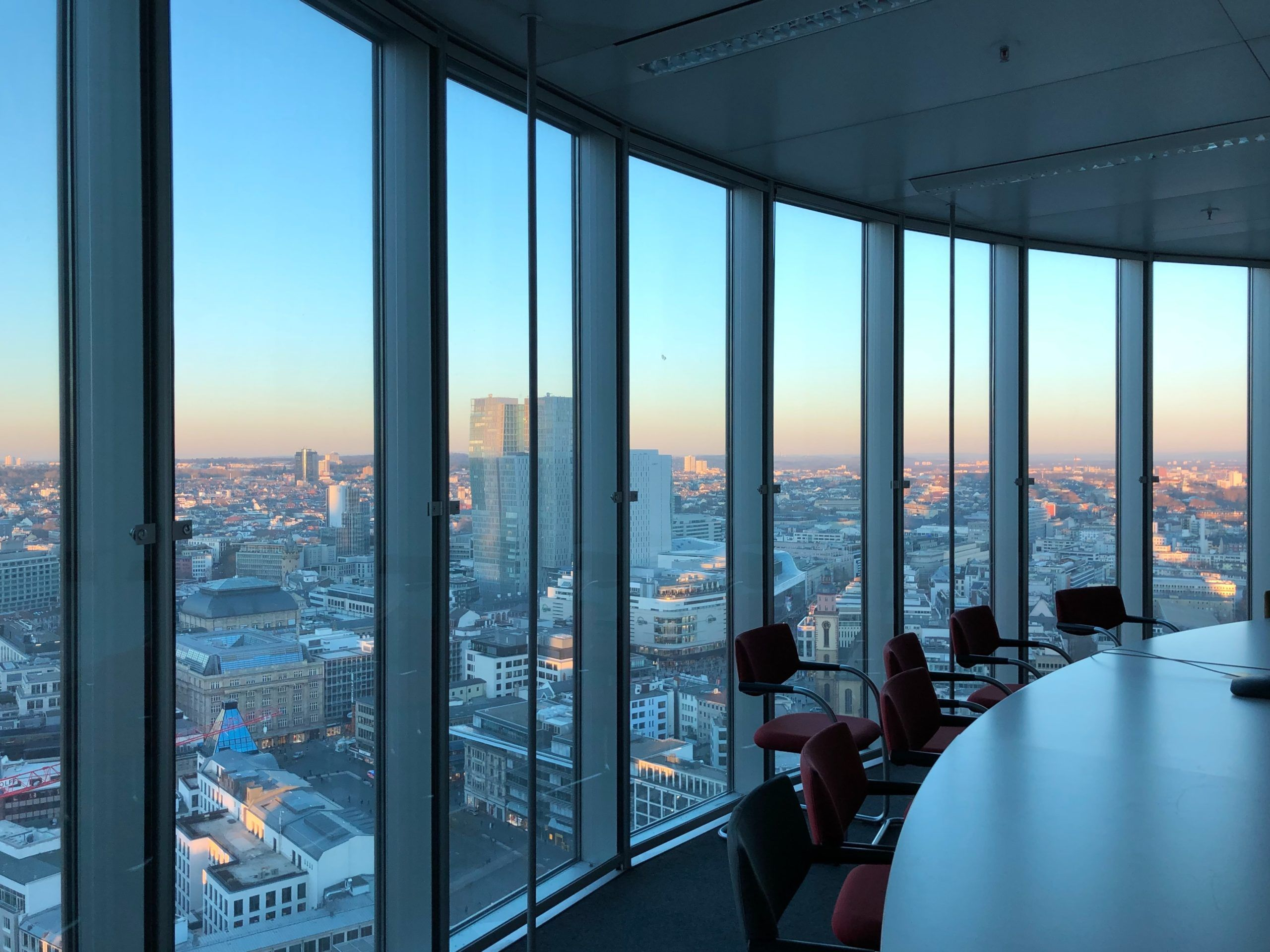 Photo of a board room with glass windows overlooking a city skyline.